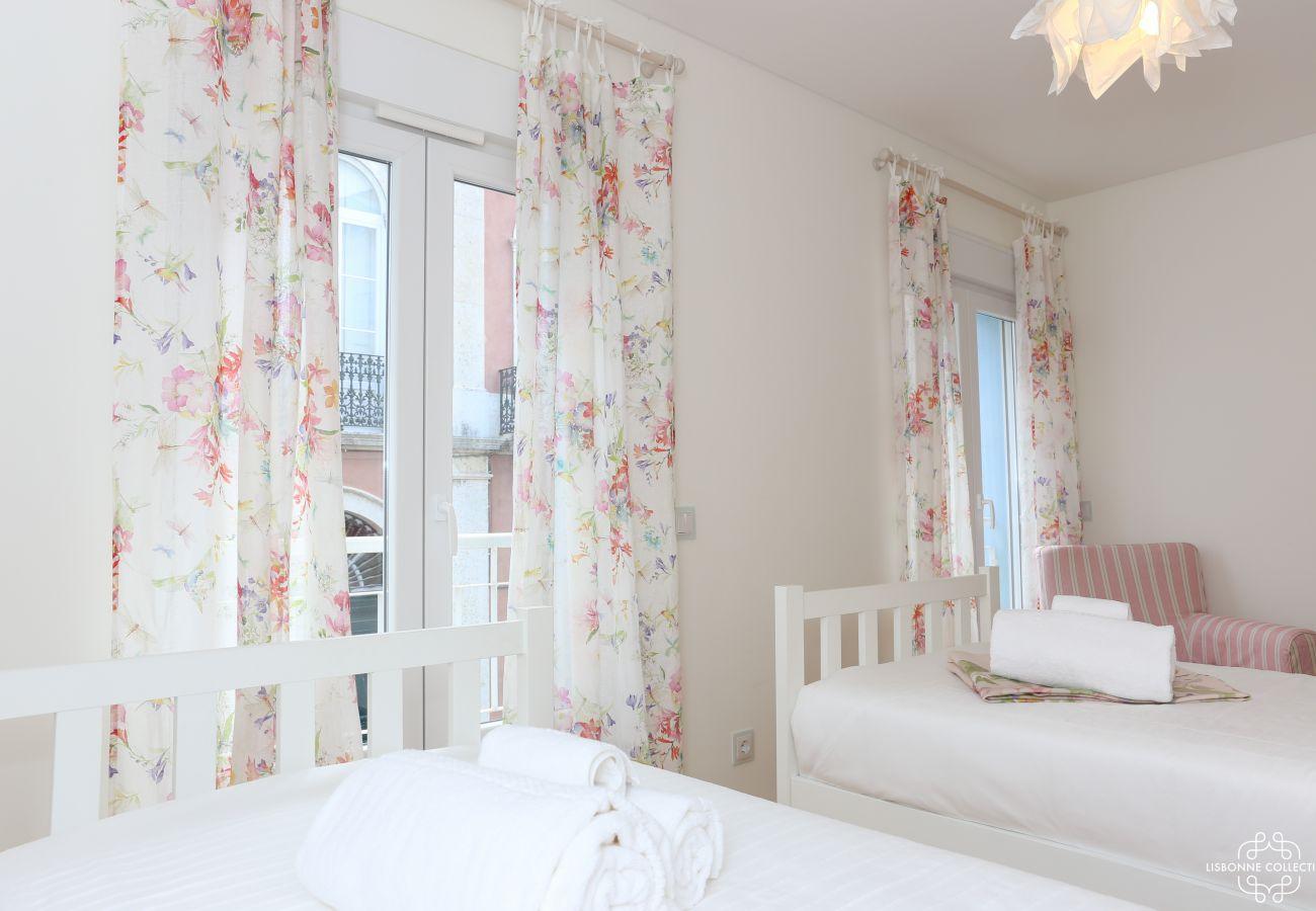 Chambre de luxe avec deux lit simple, un canapé simple et accès au balcon