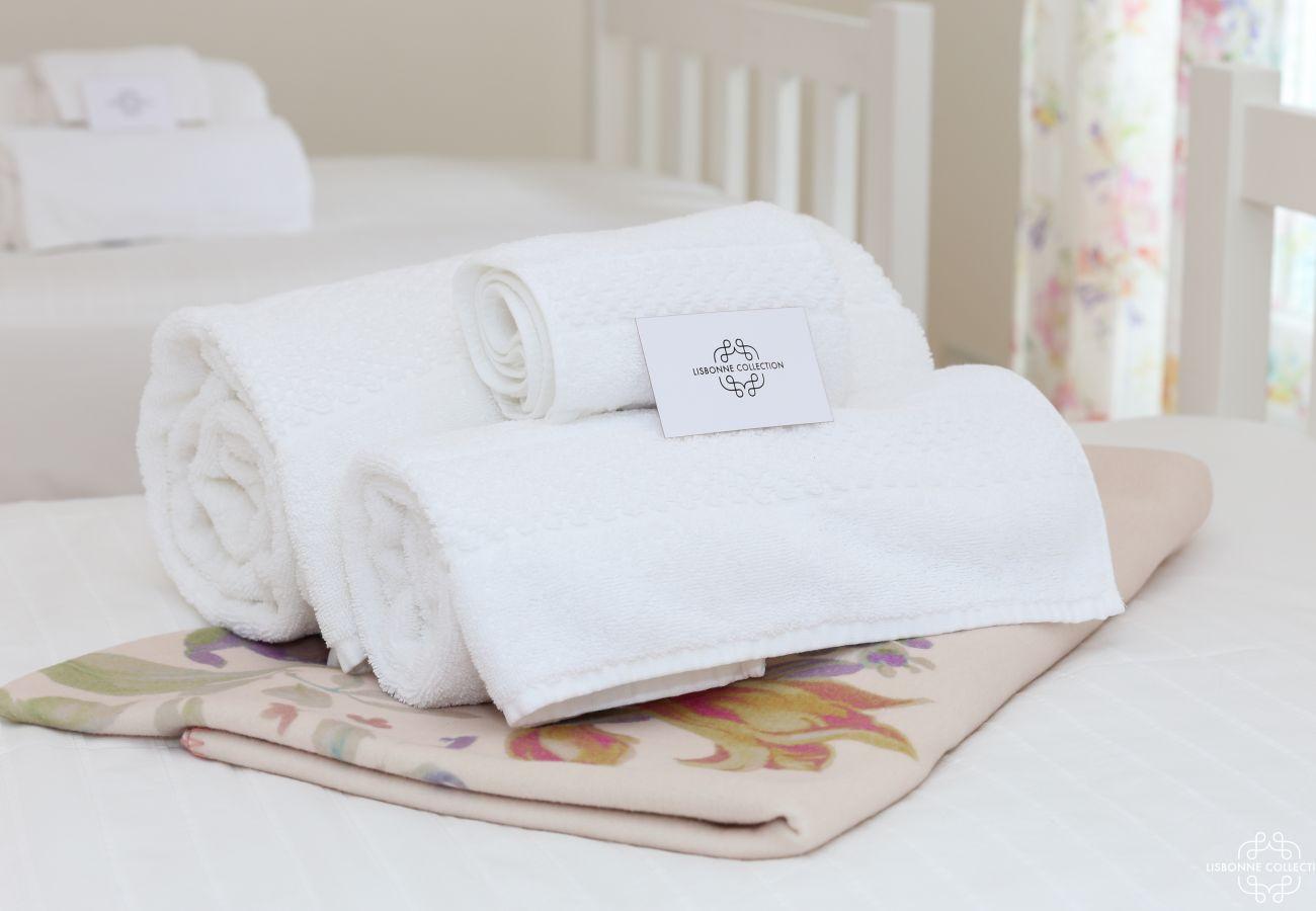 Serviette de bain pliées et posées sur le lit avec carton