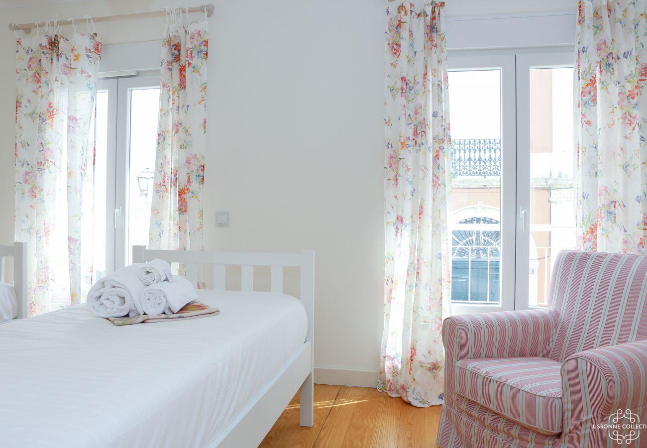 Chambre lumineuse avec deux lit simple, un canapé simple et accès au balcon