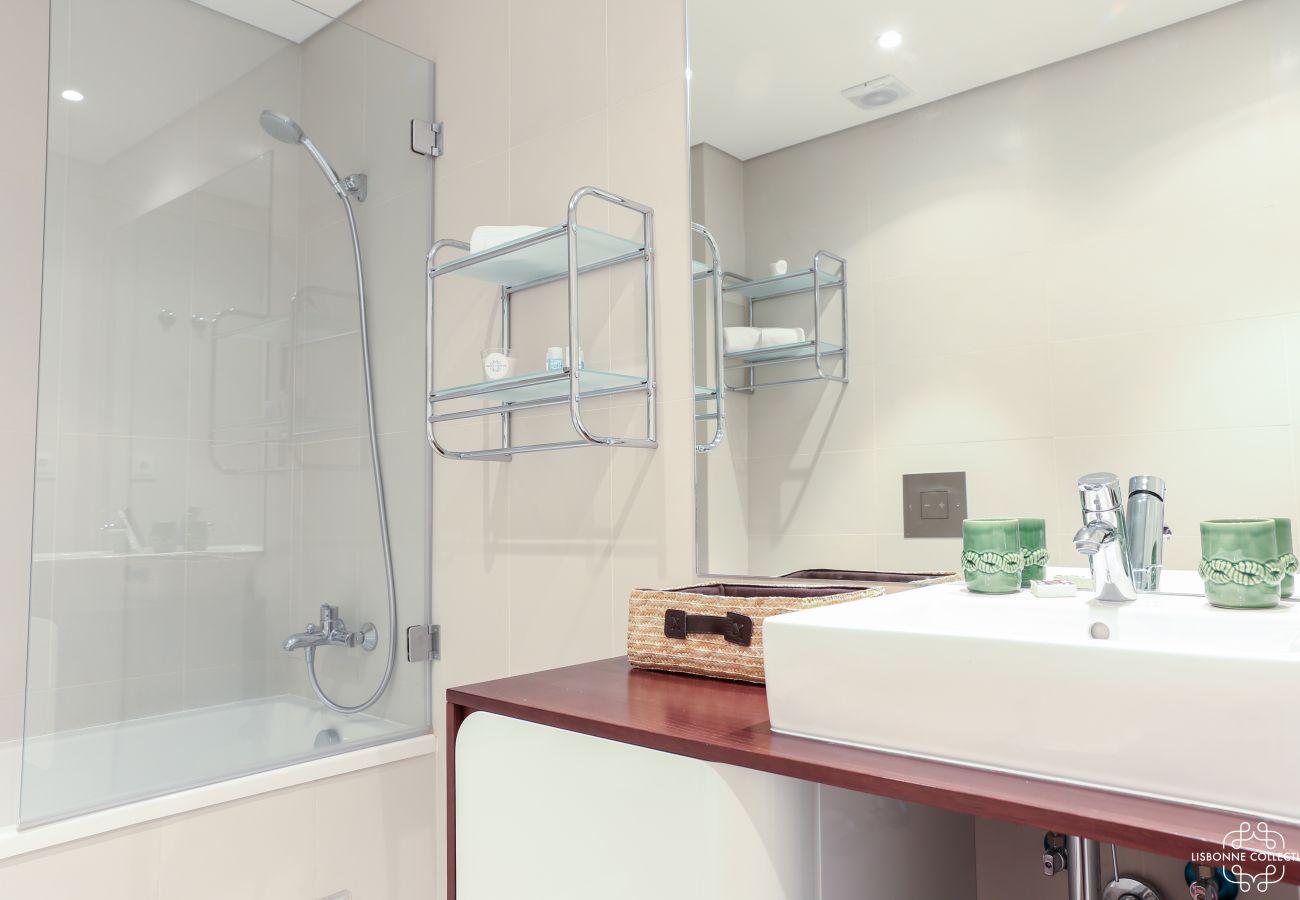 Salle de bain moderne avec baignoire et vasque en céramique et un meuble en bois
