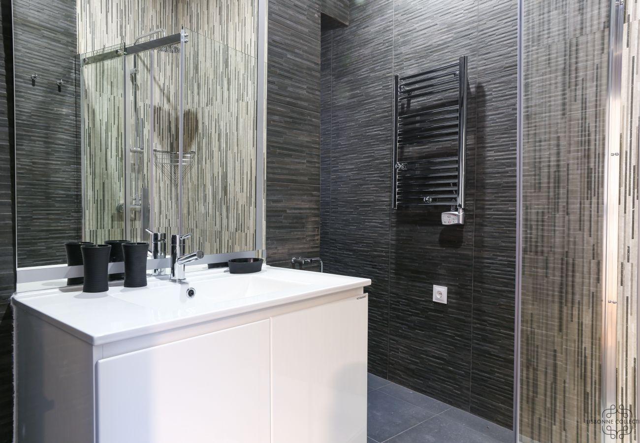 douche spacieuse et moderne avec vasque, toilette et radiateur et sèche-serviette