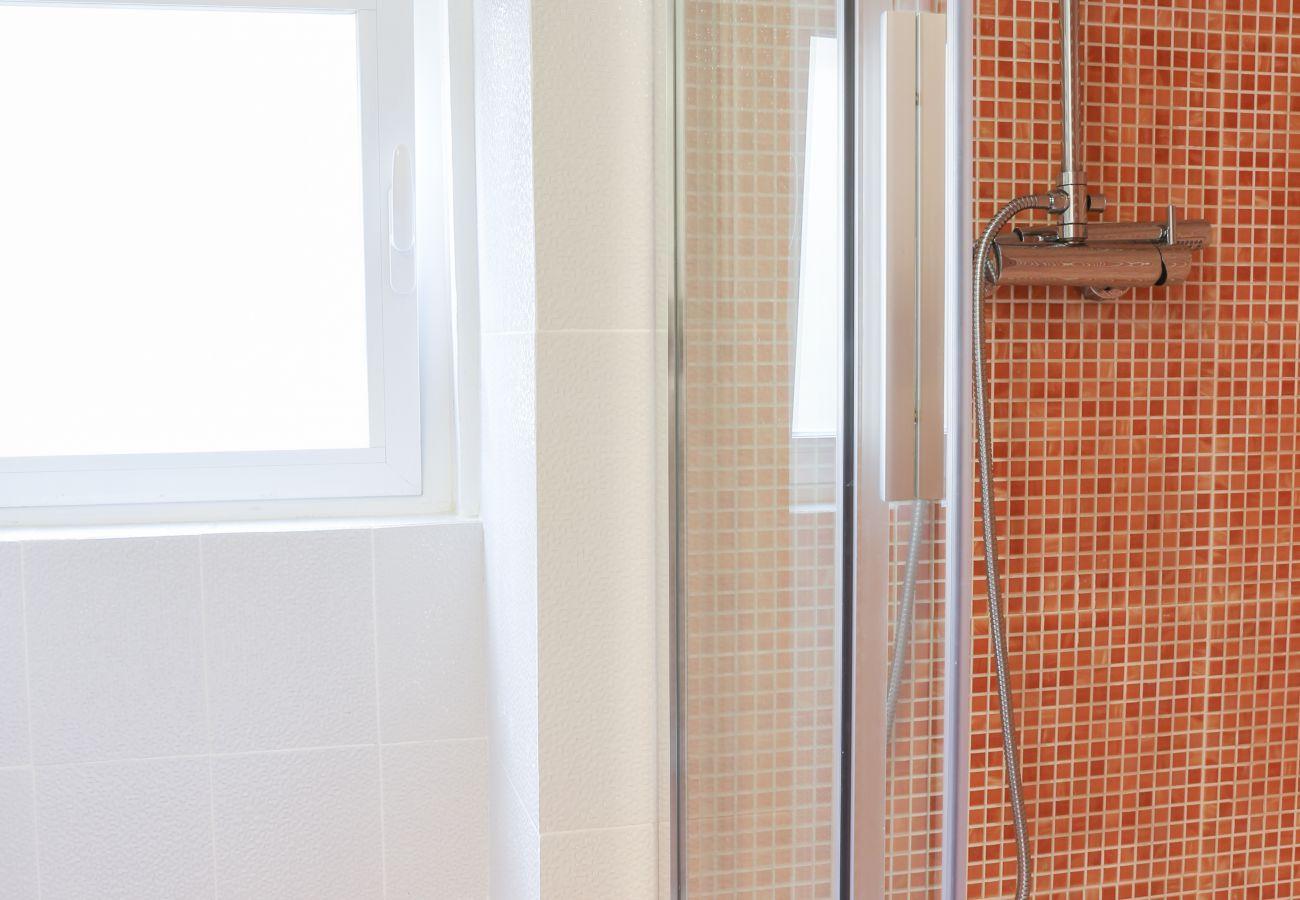 douche lumineuse avec fenêtre dans la salle de bain