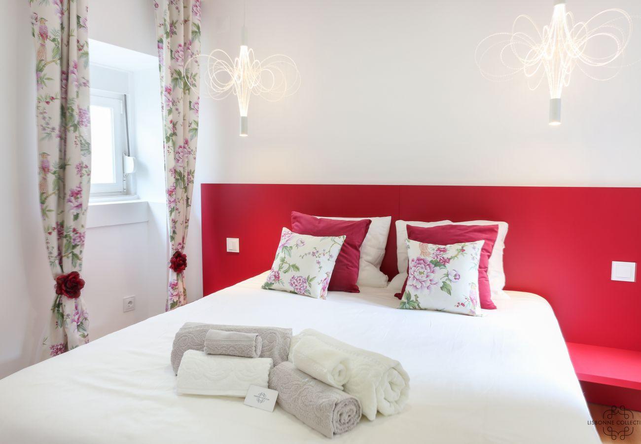 chambre principale colorée et épurée avec serviettes pliées sur le lit
