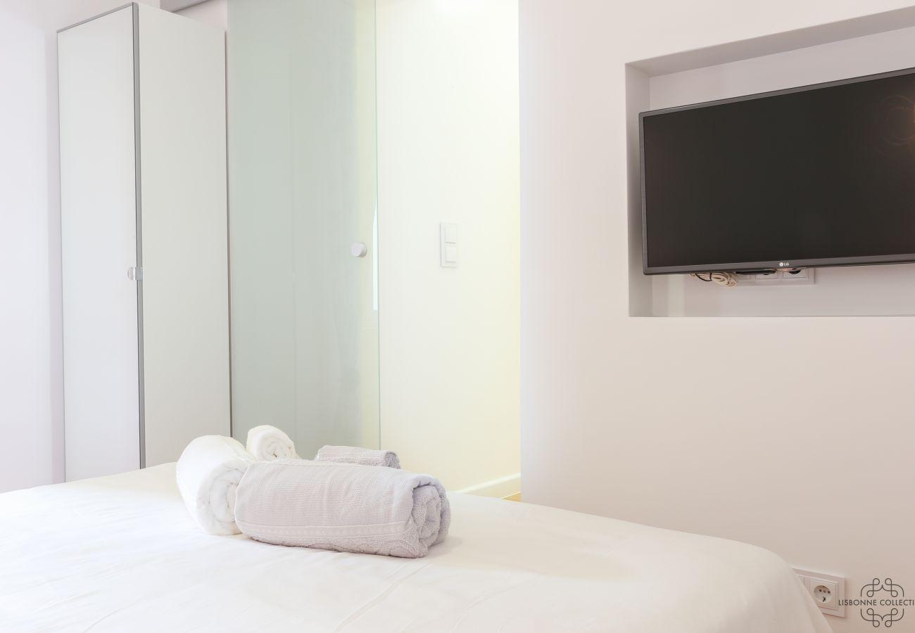 chambre cosy lumineuse avec TV incrustée dans le mur en face du lit