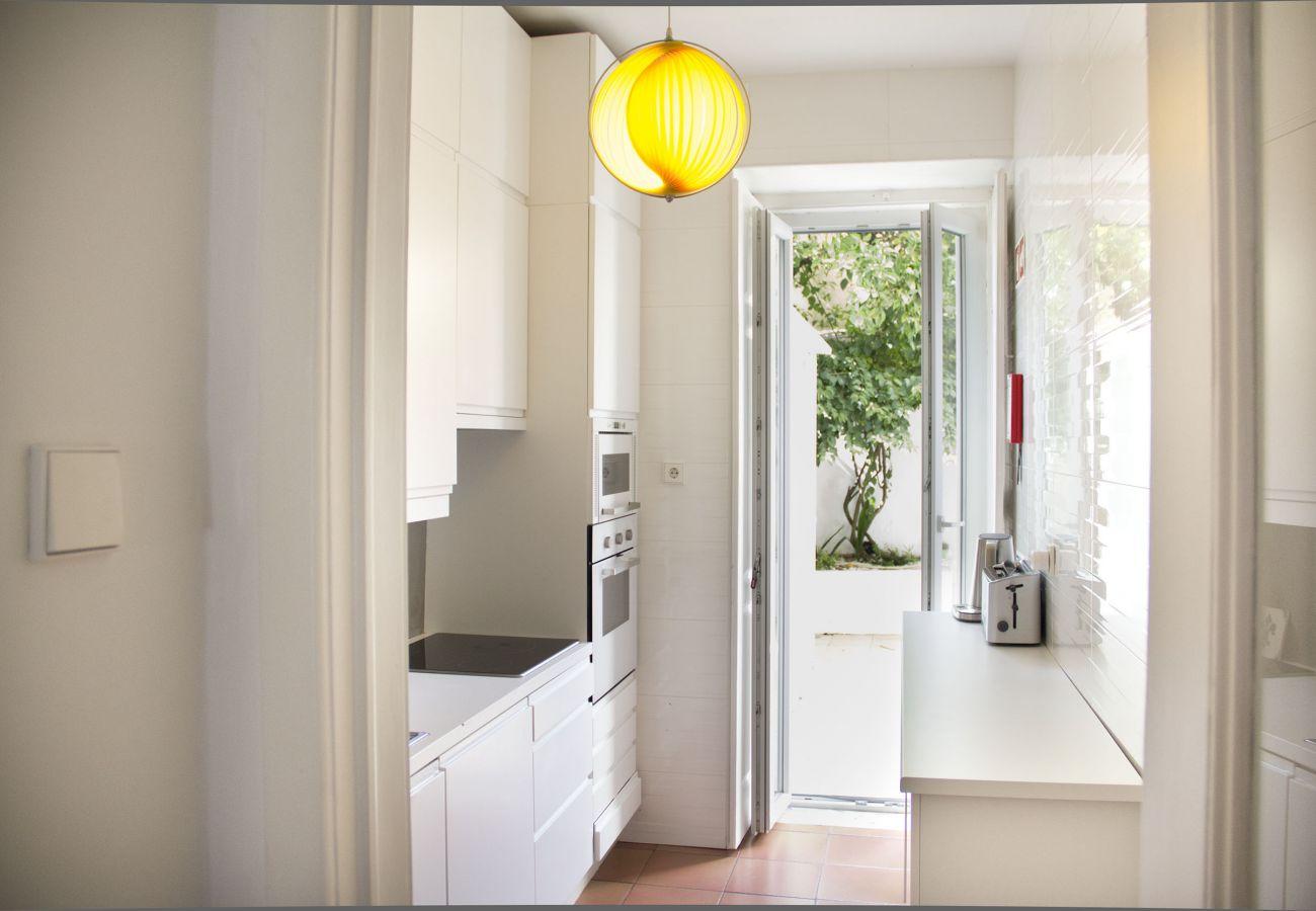 cuisine lumineuse de Lisbonne ouvrant sur une patio intérieur cosy et fleuri