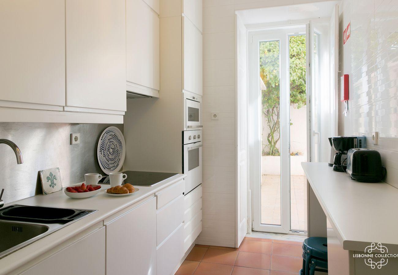 cuisine haut de gamme avec four, microonde, plaques de cuisson ouvrant sur une patio intérieur cosy et fleuri