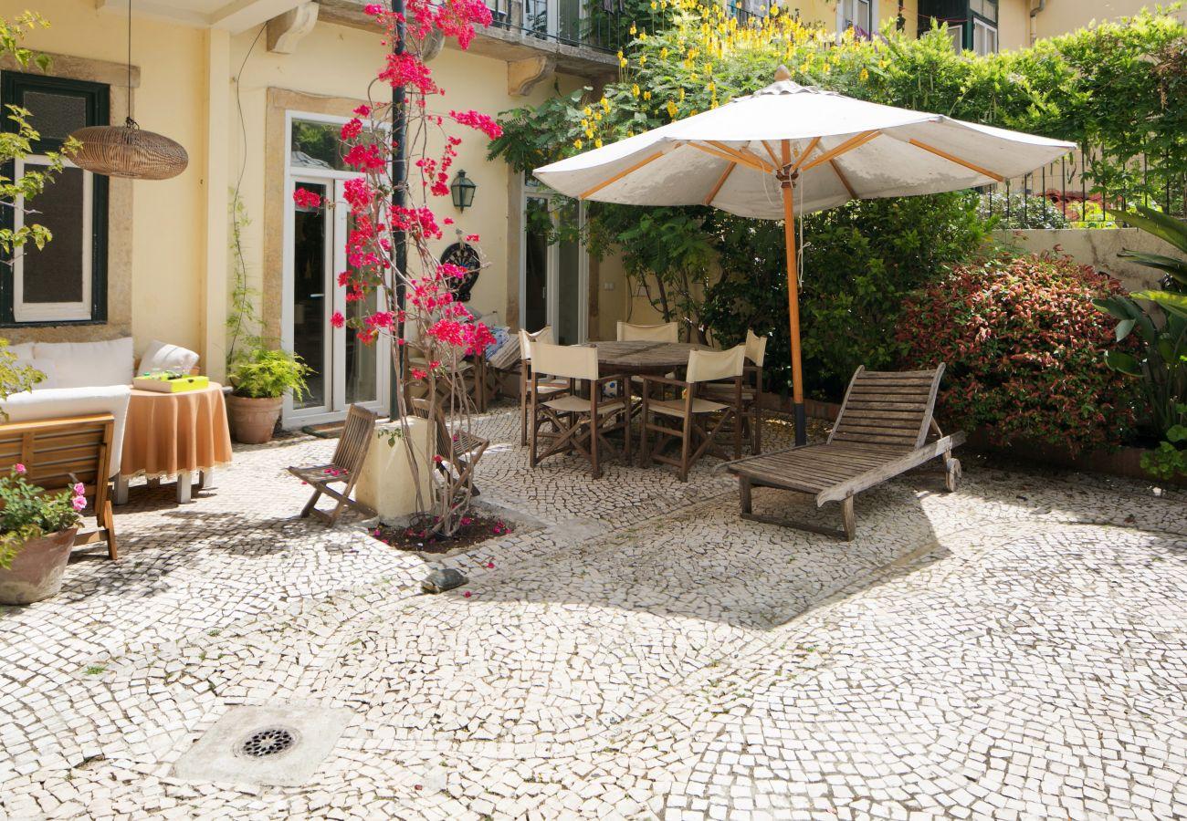 jardin typique et chaleureux en plein centre de Lisbonne avec table et chaises longues