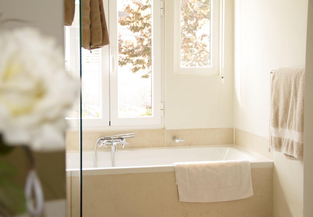 salle de bain avec baignoire aux tons épurés avec vue sur le patio intérieur