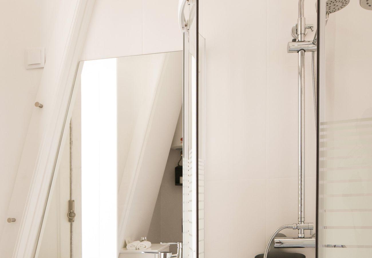 Salle de bain lumineuse avec douche et grande fenêtre