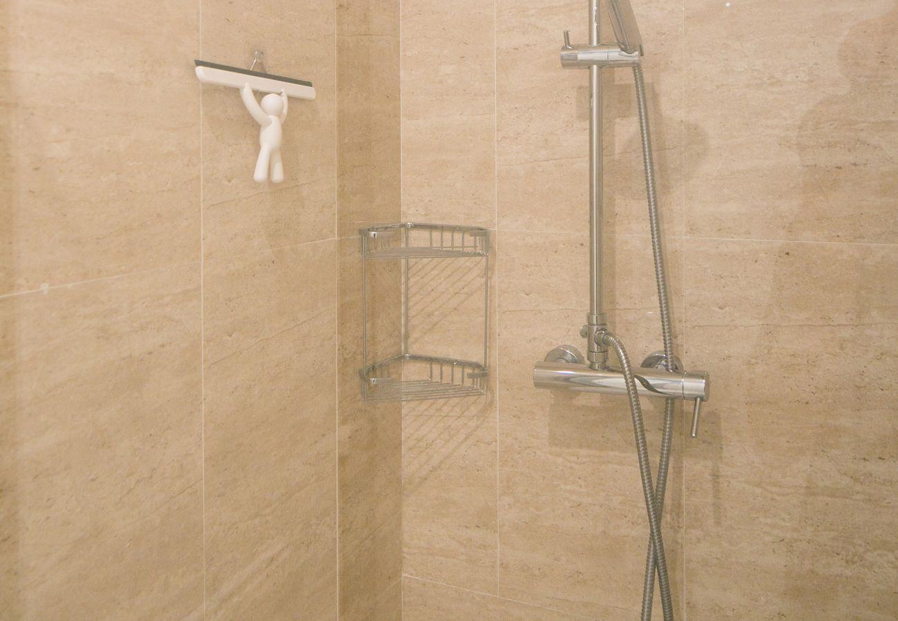 Douche spacieuse et moderne avec vasque, toilette et radiateur sèche-serviette