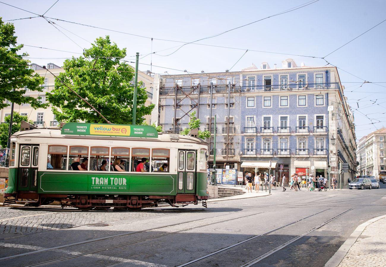 Grande place à Lisbonne avec un tram typique de la capital portugaise.