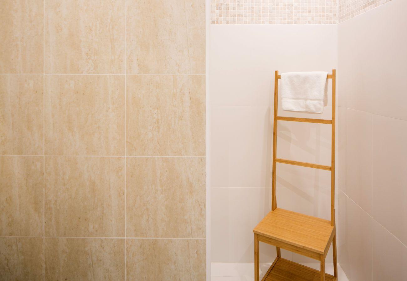 Sèche serviette devant une douche au coeur d'une salle de bain
