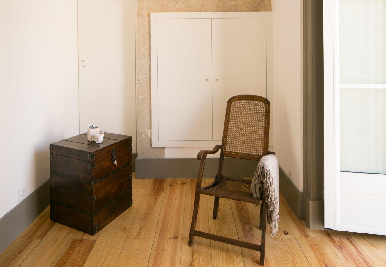 Décoration avec chaise rustique et table de chevet en bois devant une fenêtre