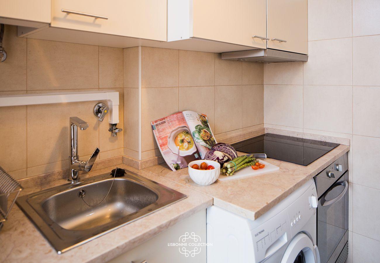 Salle à manger avec machine à laver, four, évier, le tout communiquant sur le couloir