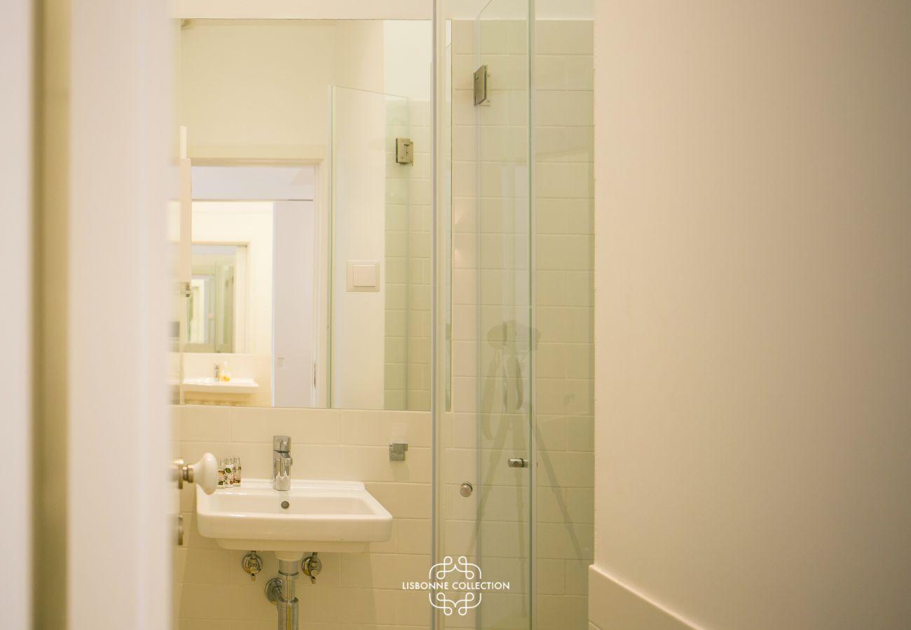 Salle de bain resplendissante avec douche et vasque aux tons joyeux