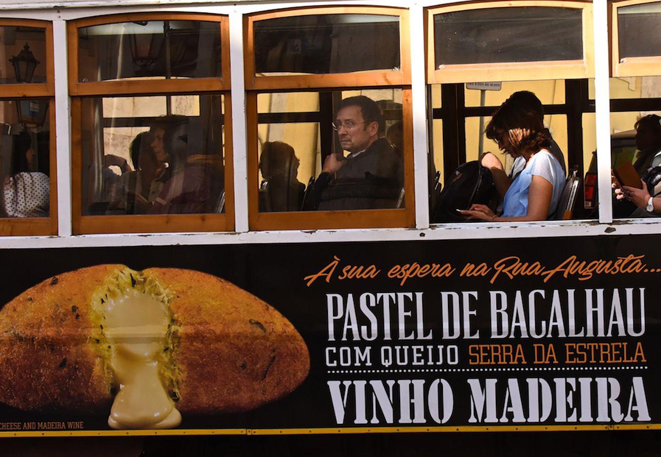 Tram typique chargé de touristes avec publicité dessus