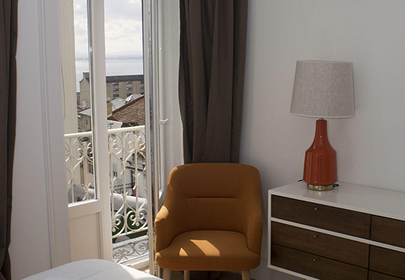 Fauteuil et lampe posée sur le meuble de la chambre
