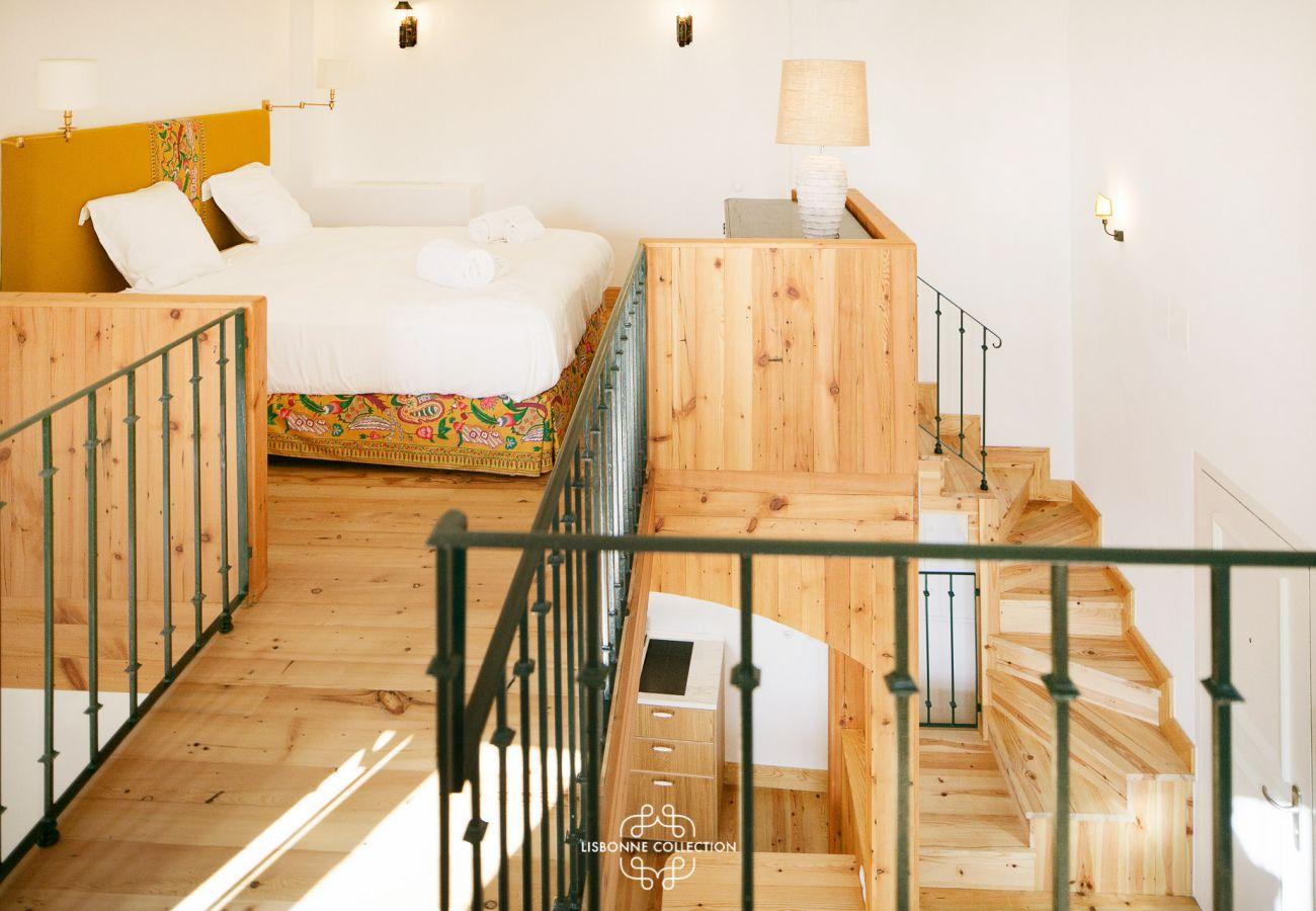 Salon et cuisine avec une mezzanine donnant accès à la chambre