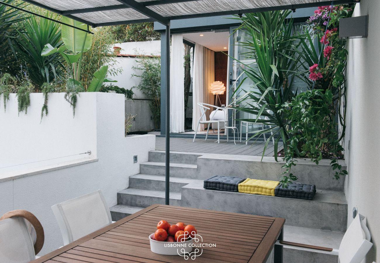 Esplanade aménagée avec des plantes et de grandes baies vitrée