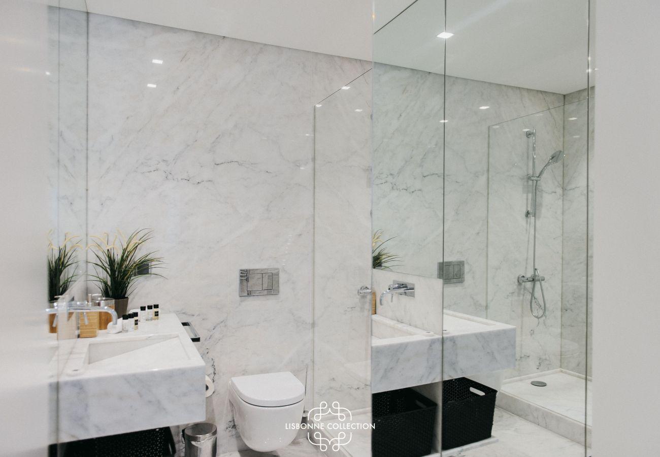 Salle d'eau de prestige en marbre avec douche, toilette et vasque