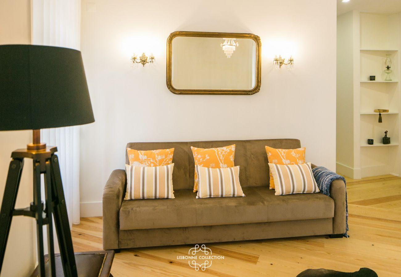 salon avec canapé, lampe design et vieux parquet à Lisbonne