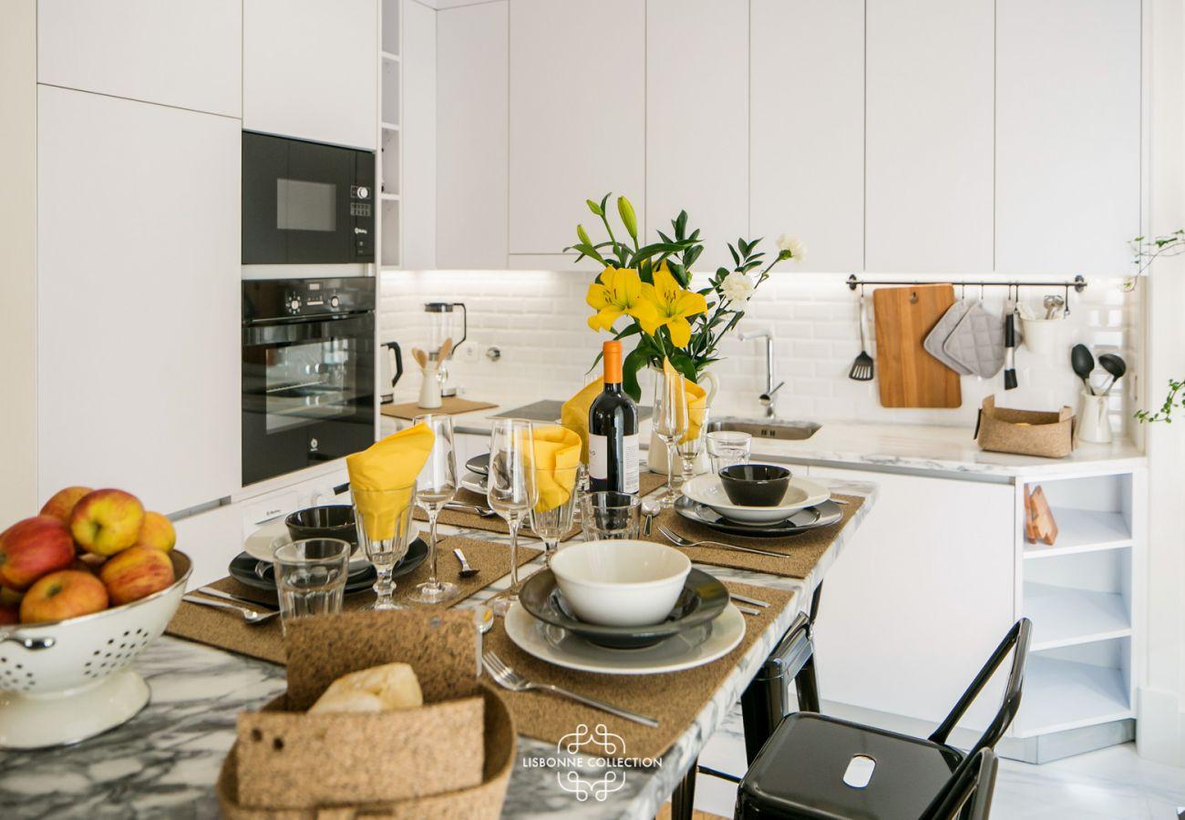 table dressée avec vue sur la cuisine toute équipée