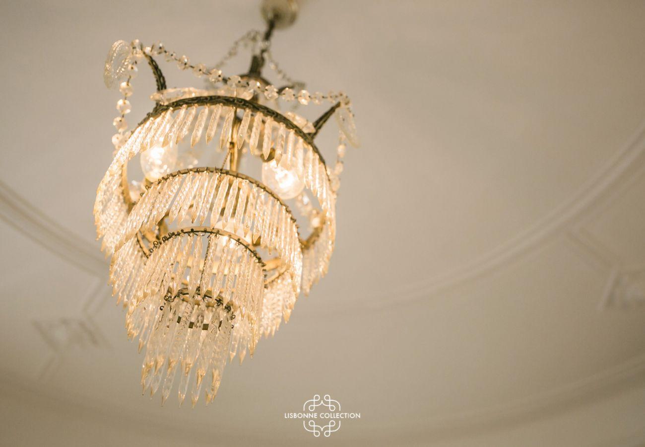 lustre en cristal suspendu sur un plafond à moulure typiquement lisboète