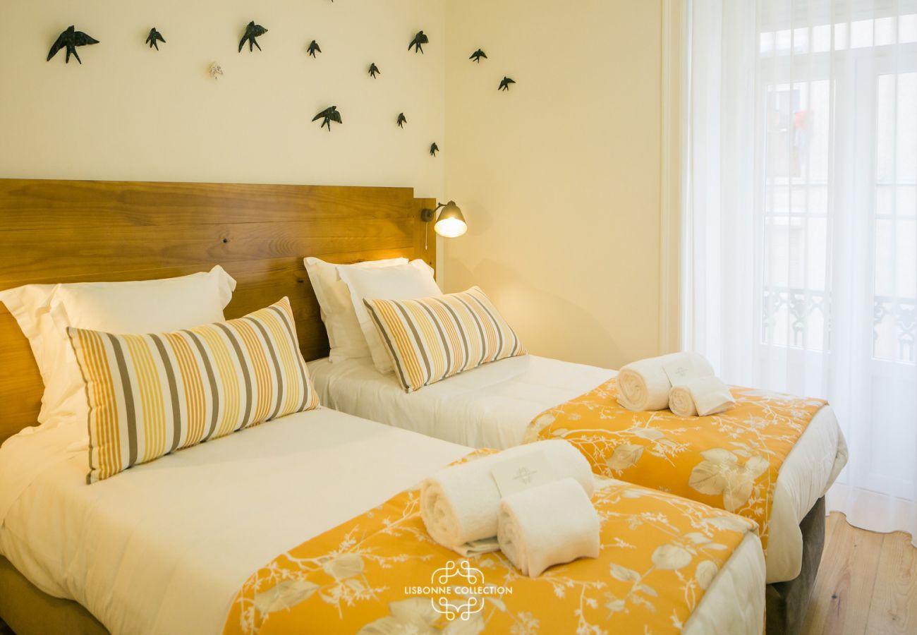 2 lits simple avec plaid jaune et hirondelles sur le mur