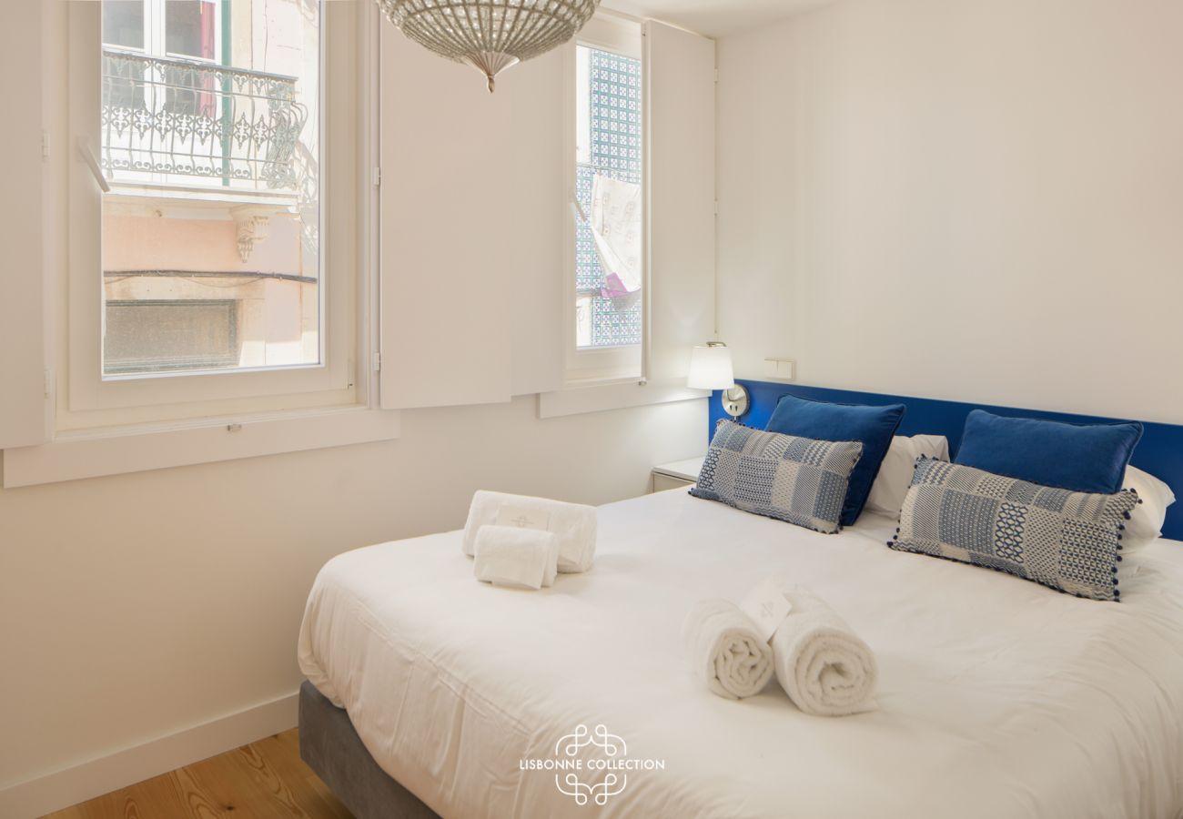 Chambre principale à dominante bleu et blanche avec grande fenêtre