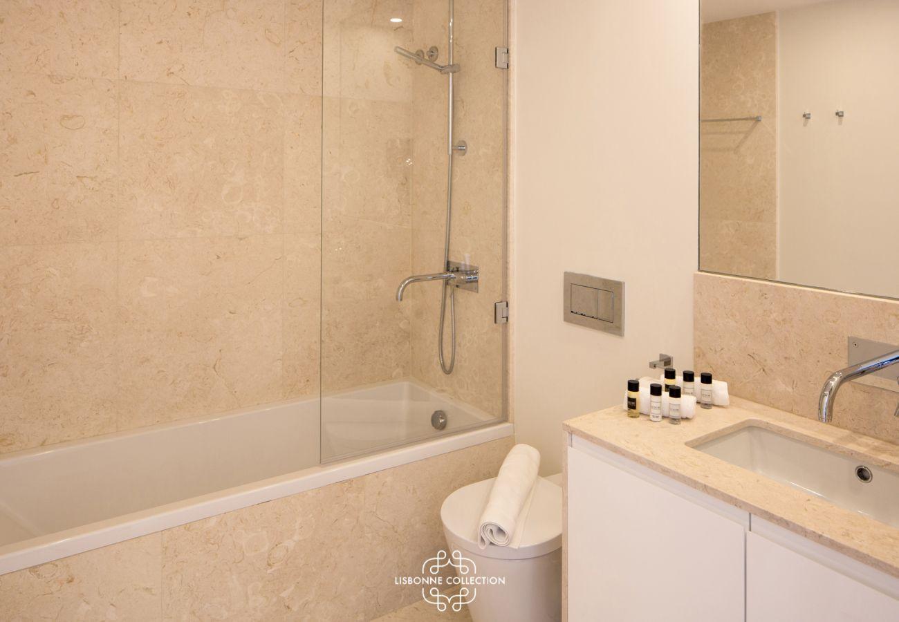 Salle de bain en marbre beige avec baignoire et grande vasque