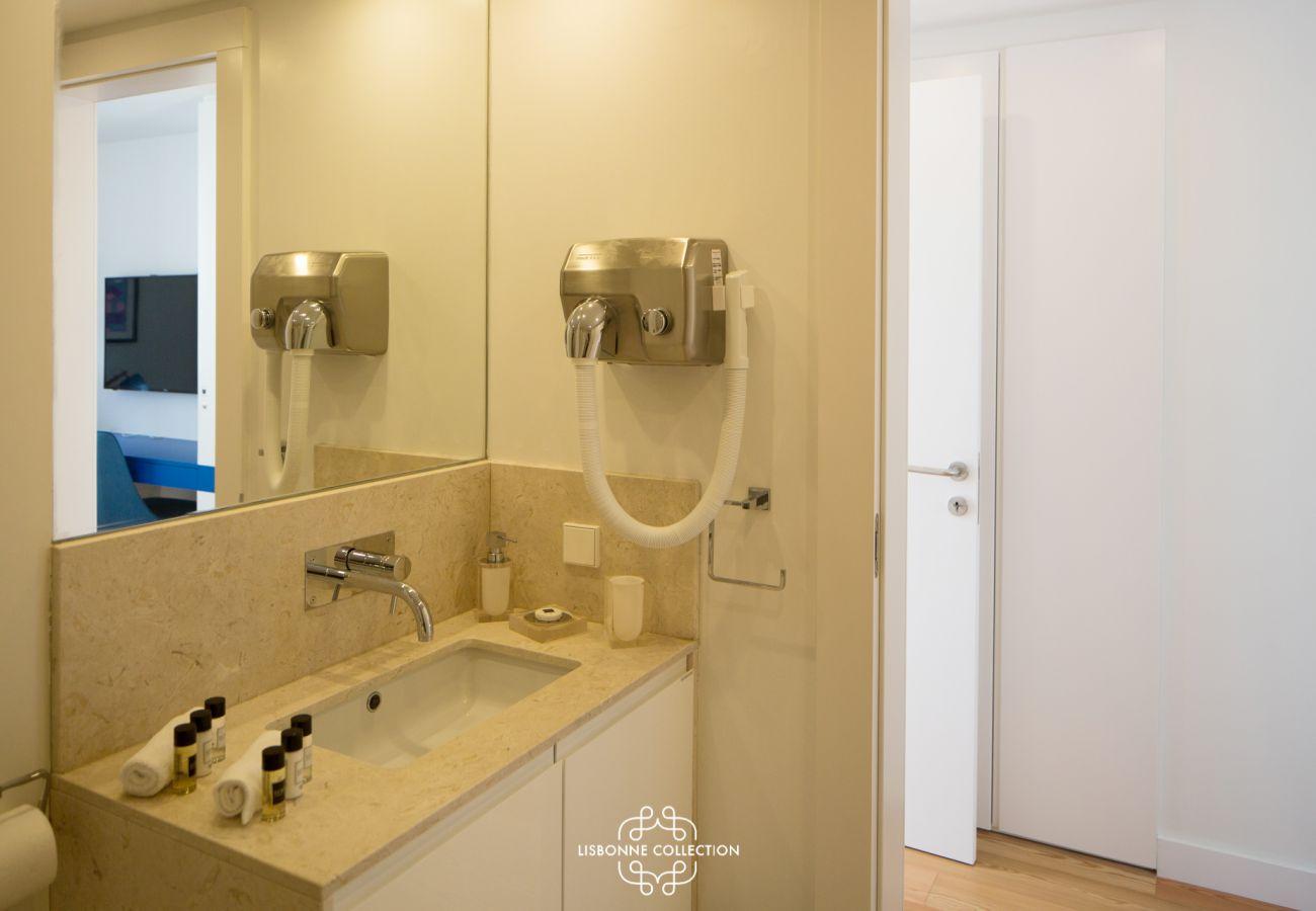 Salle de bain avec grand miroir, vasque en pierre de marbre et sèche-cheveux