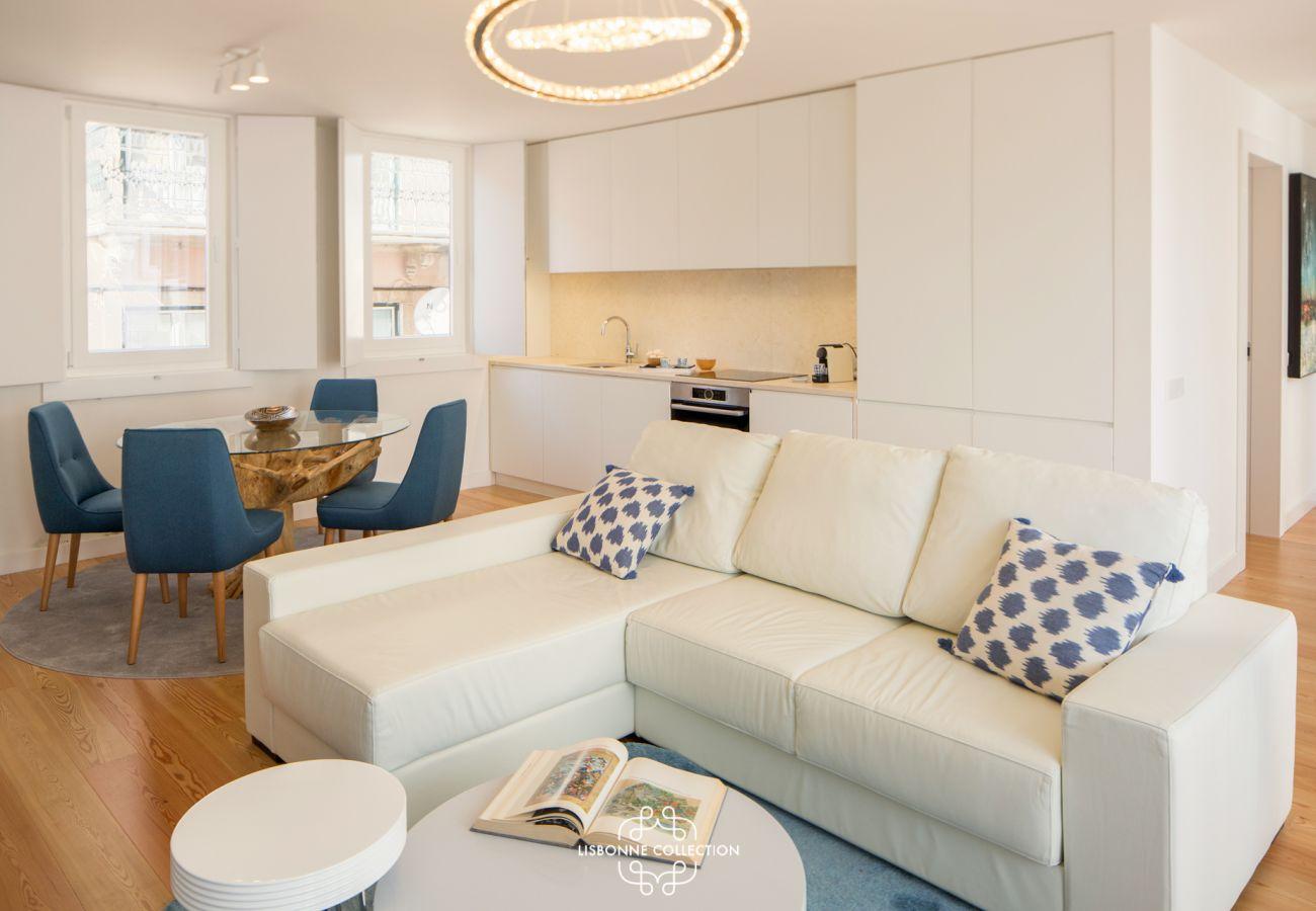 Grand canapé blanc près du corridor principal donnant sur le reste de l'appartement