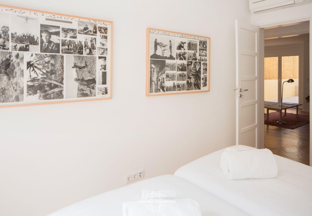 Chambre avec deux lits simples avec des photos historiques sur les murs