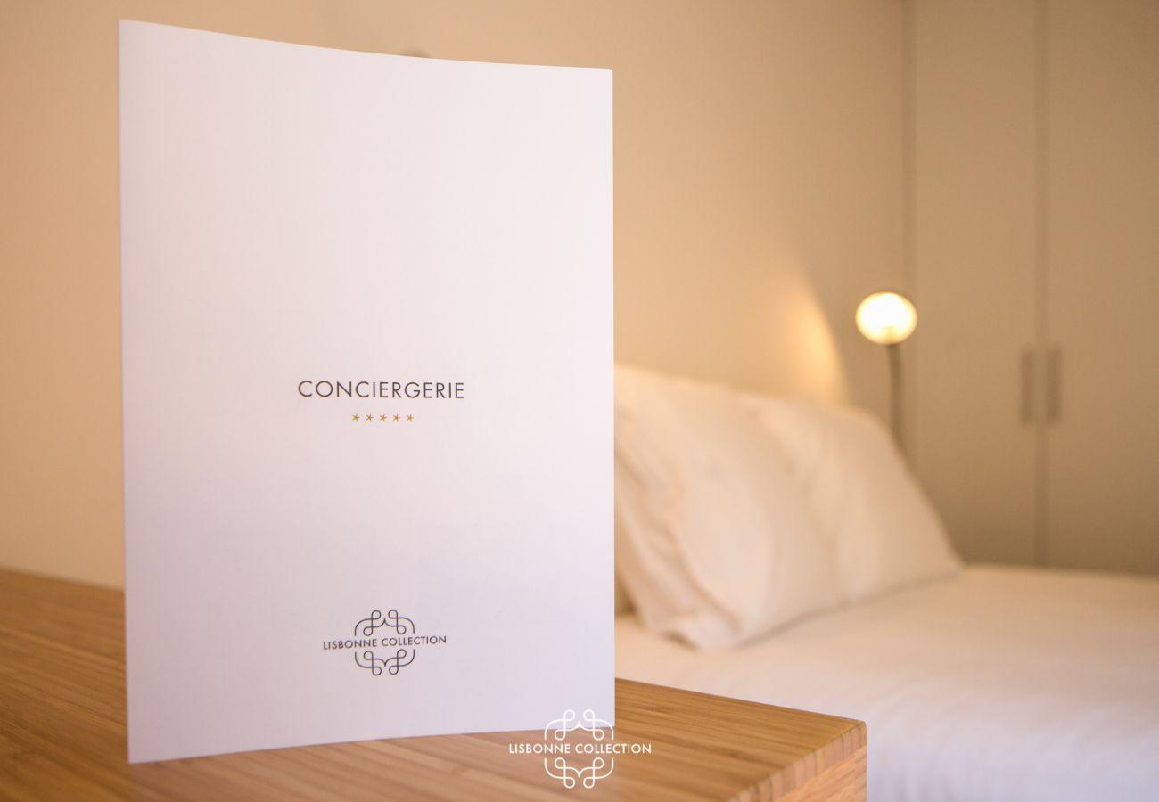 Plaquette des services conciergerie sur table de chevet près du lit double