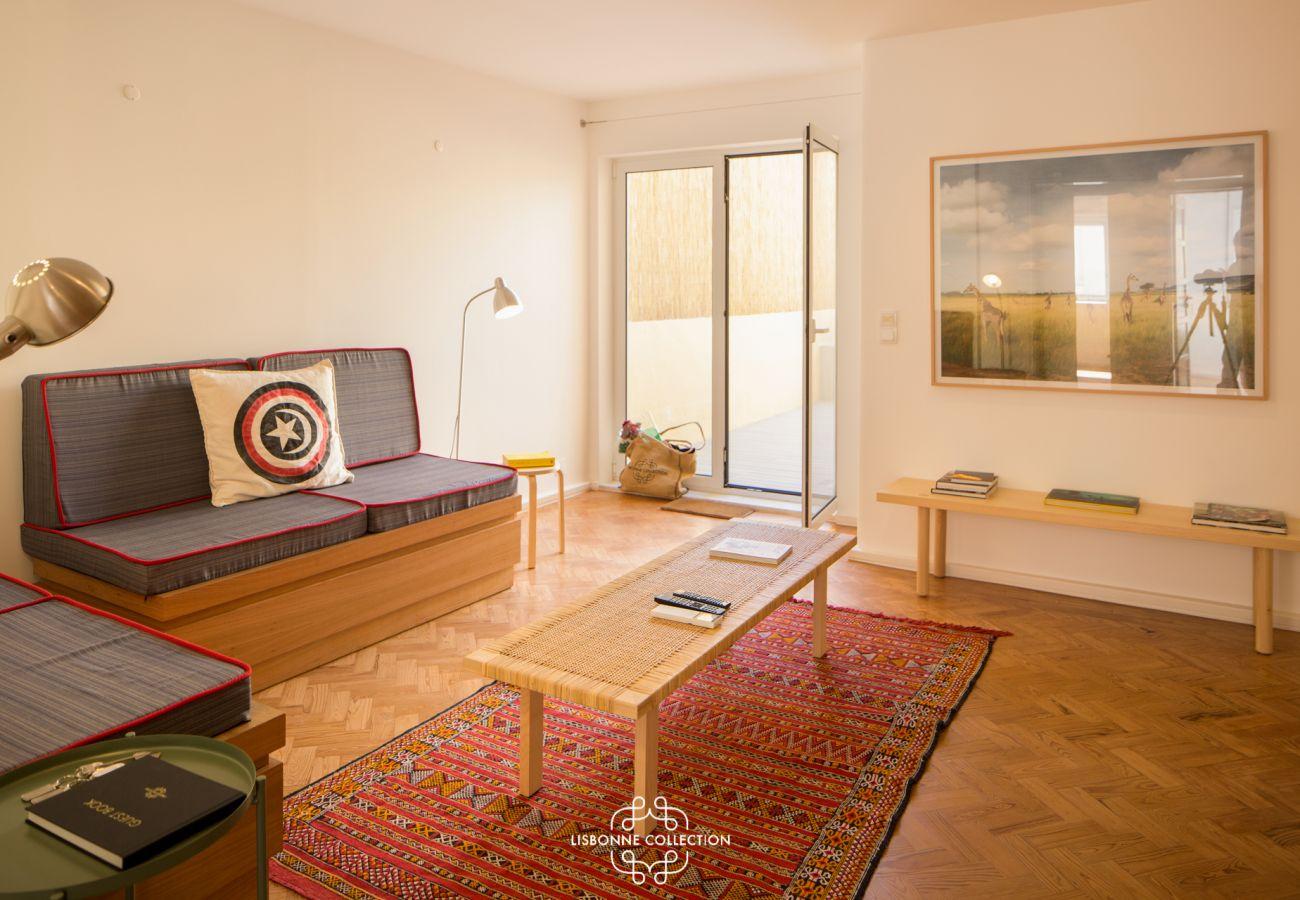 Séjour avec canapé, accès à la cuisine et à la terrasse aux couleurs éclatantes