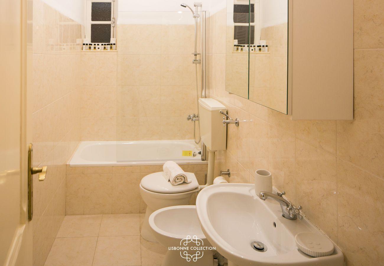 salle de bain beige avec grande baignoire, bidet et vasque