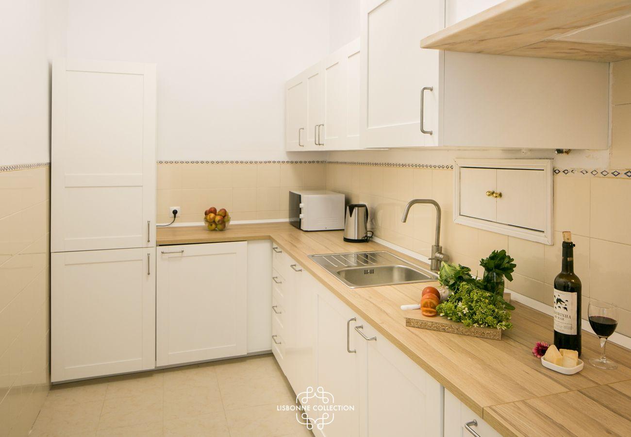grande cuisine lumineuse avec plan de travail en bois et bouteille de vin