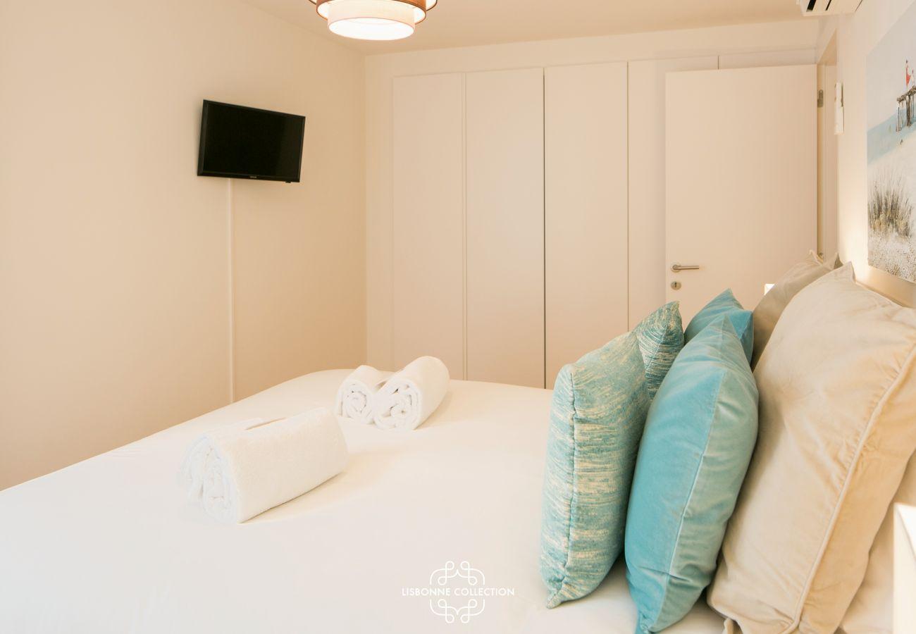 Coussins bleus empilés sur le lit aux draps blancs