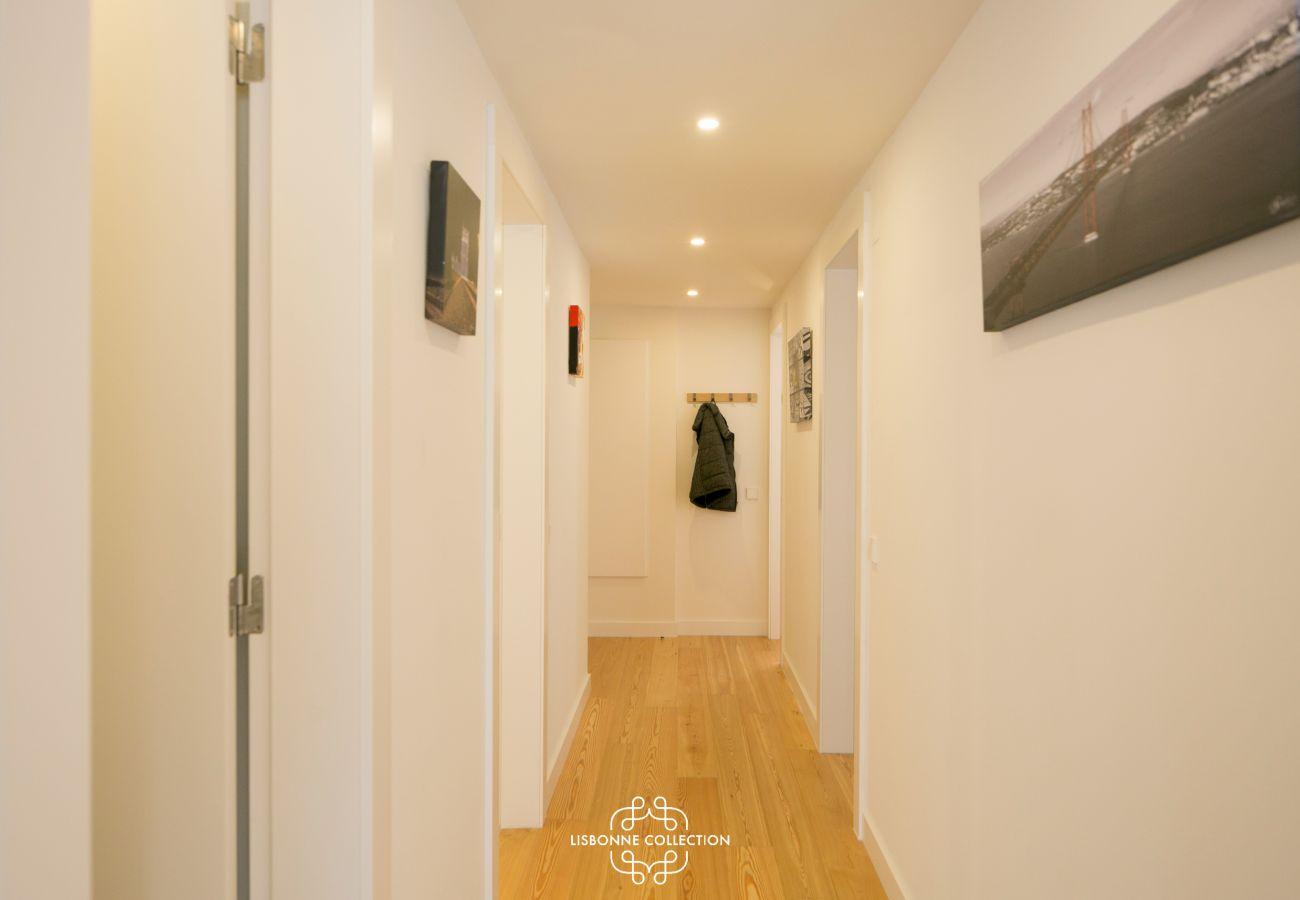 grand couloir avec murs et portes blanches et sol en bois