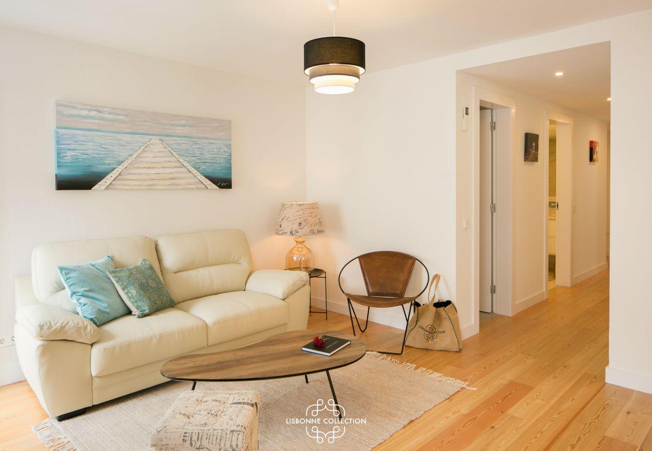 Salon équipé d'un canapé avec accès sur le couloir de l'entrée de l'appartement