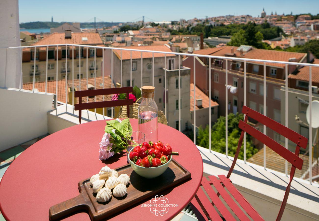 terrasse aménagée avec mobilier rouge et large panorama sur Lisbonne